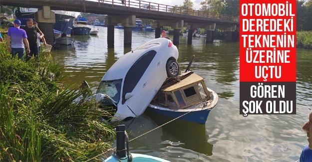 Otomobil deredeki teknenin üzerine uçtu